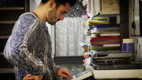 Man using photocopier. Handsome young man in jumper standing near photocopier and using it Royalty Free Stock Photos