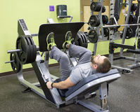 Man Using Plate Loaded Leg Press Stock Image