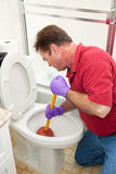 Man Using Plunger in Toilet Royalty Free Stock Photography