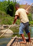 Man using pole to sail the bamboo raft in the river. One of career for tourism at Chiang Mai province in Thailand.Jungle and stock images