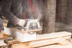 Man Using Power Saw to Cut Planks of Wood Royalty Free Stock Photo