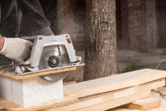 Man Using Power Saw to Cut Planks of Wood Stock Images