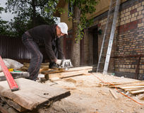 Man Using Power Saw to Cut Planks of Wood Royalty Free Stock Image