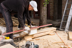 Man Using Power Saw to Cut Planks of Wood Stock Image