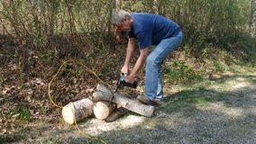 A man using a power saw to cut wood. A camper cutting a tree trunk to be used for firewood stock footage