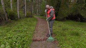 Man using rake on path stock video