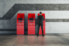 Man using red ATM machine Stock Photography