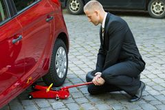 Man using red hydraulic floor jack for car repairing. Man Trying To Lift The Car With Red Hydraulic Floor Jack For Repairing stock photo
