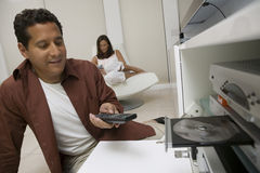 Man Using Remote Control To Insert DVD At Home. Man using remote control to insert DVD in the living room at home royalty free stock photo