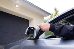 Man by using remote  opens garage. Man by using remote garage opens in a cloudy day Royalty Free Stock Image