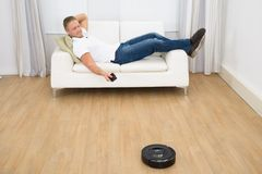Man using robotic vacuum cleaner remote control Stock Images