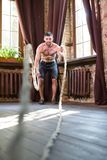 Man using ropes to do workout on arm and shoulder muscles. Athlete male spending free time at home to do sport exercises royalty free stock photos