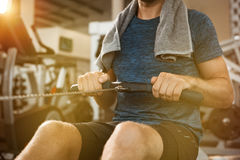 Man using row machine. Young man working out with row machine at gym. Athletic man using rowing machine in the gym. Close up hand of fit man training at gym Royalty Free Stock Photos