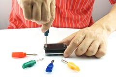 Man using screwdriver for repair. Man using screwdriver with screw for minor repair with white background Royalty Free Stock Photo