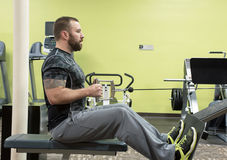 Man Using Seated Row Machine Stock Image
