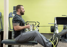 Man Using Seated Row Machine. Man sitting in good form as he uses the seated row machine royalty free stock image