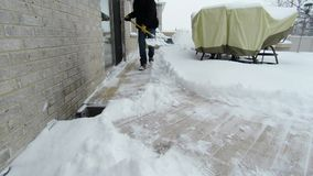 Man using shovel to remove snow after a winter storm stock footage