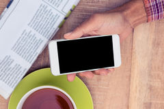 Man using smart phone by coffee and newspaper on table Stock Image