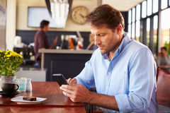 Man using smart phone in a coffee shop Stock Image