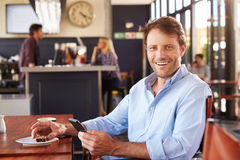 Man using smart phone in a coffee shop, portrait Royalty Free Stock Photos