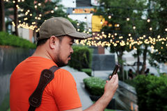 Man using Smart phone in hand with bokeh in park background. And have some space for write wording Stock Photography