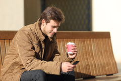 Man using a smart phone and holding a coffee cup Stock Photography
