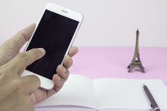 Man using smart phone with notebook, pencil and souvenir Eiffel Royalty Free Stock Photo