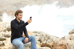 Man using a smart phone in winter on the beach Stock Photo