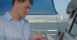 Man using smart phone on the yacht. Young man typing on cellphone while traveling by ship. Sea and coastal city in background stock footage