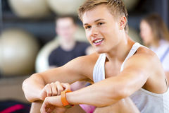 Man Using Smart Watch While Looking Away In Gym Stock Photo