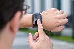 Man using smart watch. Outdoors Royalty Free Stock Image