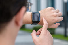 Man using smart watch. Outdoors Stock Photography
