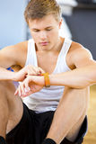 Man Using Smart Watch While Sitting In Gym Royalty Free Stock Photo