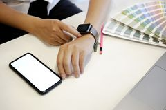 Man using a smart watch at desk in office. Man using smart watch and smart phone in designer studio Royalty Free Stock Image