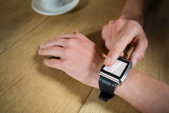 Man using smart watch at table in coffee shop Royalty Free Stock Photo