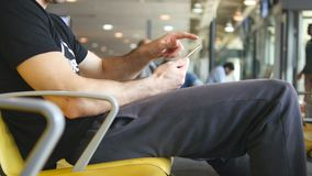 Man using smartphone in airport waiting lounge. Male hand with smart phone at terminal during expectations of flight. Close up stock footage