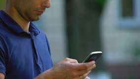 Man using smartphone application outdoors, social networks, browsing internet stock video footage