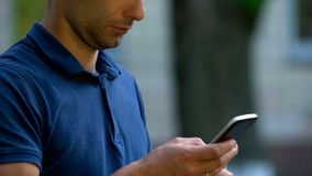 Man using smartphone application outdoors, social networks, browsing internet stock images