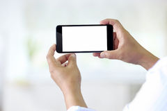 Man using smartphone on blur background. Blank screen smartphone for Graphic display montage Stock Image