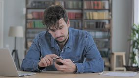 Man Using Smartphone, Browsing online at Work stock footage