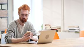 Man Using Smartphone, Browsing online at Work. Young creative designer , good looking stock footage