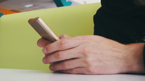 Man Using a Smartphone in Cafe. Man holds a Mobile Phone in his hands and controls his finger gestures and looks at social networks. Looking through screen stock video footage