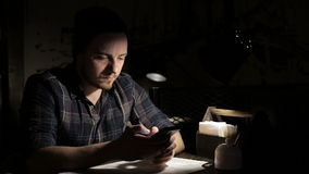 Man using smartphone in cafe in the night. Young man using smartphone in cafe in the evening stock footage