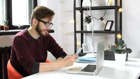 Man using smartphone and chatting, rest in office. One trendy 20s stylish guy in glasses sit at the table in art workspace and surfing on line use cellphone stock video footage