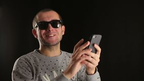Man uses smartphone and smiles stock footage