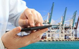Man using smartphone. Close up of businessman using smart phone for logistic business on container terminal with cranes background Royalty Free Stock Photos