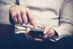 Man using smartphone. Closeup on a man's hands as he is sitting on a sofa and using a smartphone Royalty Free Stock Photography