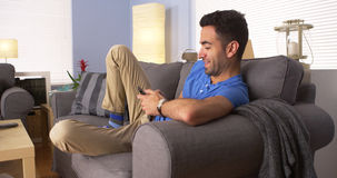 Man using smartphone on couch Royalty Free Stock Photos