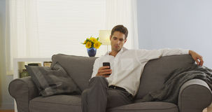 Man using smartphone on couch after work Royalty Free Stock Images
