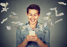 Man using smartphone with dollar bills flying away from screen. Technology online banking money transfer, e-commerce concept. Happy young man using smartphone Royalty Free Stock Images